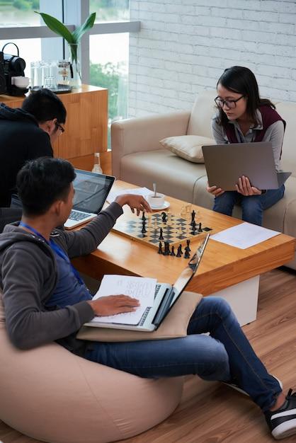 Aziatische studenten doen hun hometask en schaken Gratis Foto