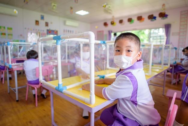Aziatische studenten in kleuterklassen op scholen in thailand dragen maskers en sociale afstand in klaslokalen Premium Foto