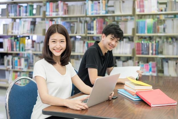 Aziatische studenten met laptop computer en boek die in bibliotheek bij universiteit spreken. Premium Foto
