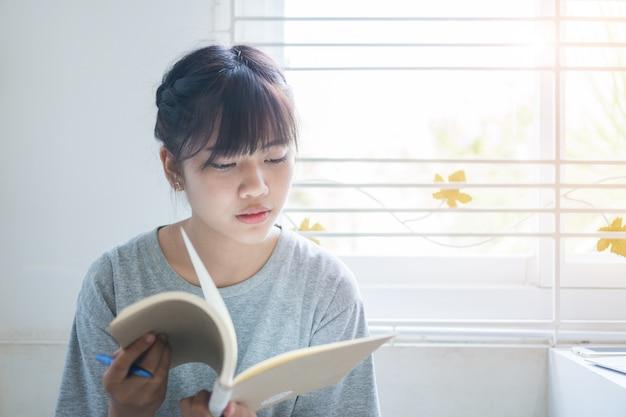 Aziatische studentennota over notitieboekje terwijl het leren van online studie of e die via laptop computer leren. Premium Foto