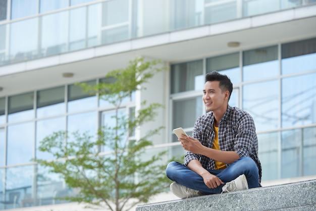 Aziatische studentenzitting op campustreden in openlucht met smartphone die in de afstand staren Gratis Foto