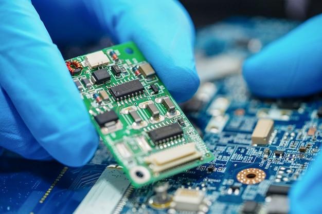 Aziatische technicus die de computer van de microkring hoofdraad herstelt. Premium Foto