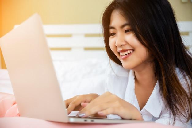 Aziatische tienerlaptop van het vrouwengebruik op bed Gratis Foto