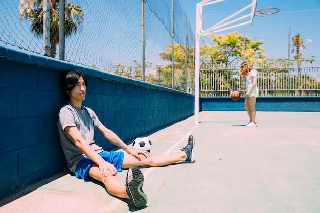 Aziatische tienerstudent die naast sportsgroundomheining rusten Gratis Foto