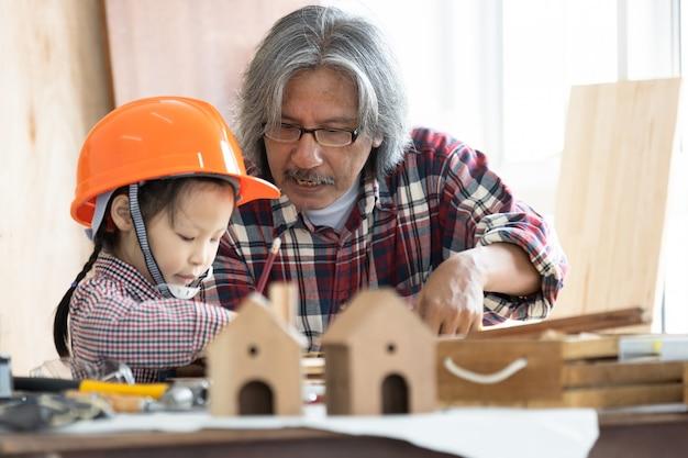 Aziatische timmerman en dochter die aan houtbewerkingslijst werken in de winkel van het huistimmerwerk Premium Foto