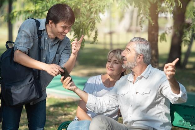 Aziatische toeristen jonge man met slimme mobiele telefoon in zijn handen vraagt om aanwijzingen van de oude blanke oudere man die bij de vrouw zit, hij wees met de vinger naar de weg. Premium Foto
