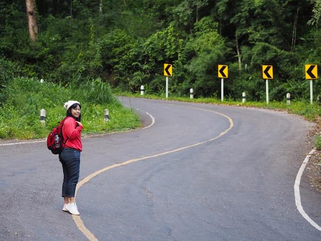Aziatische toeristenvrouw die op kronkelende weg met krommewaarschuwingsbord in het bos lopen. hipster backpacker. Premium Foto