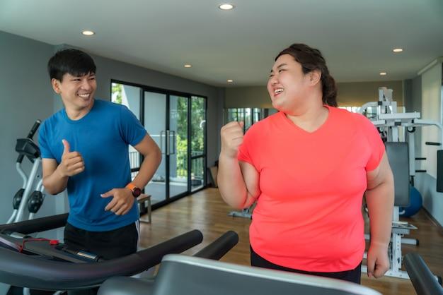 Aziatische trainerman en te zware vrouw die opleiding op tredmolen in gymnastiek uitoefenen Premium Foto