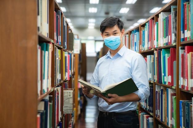 Aziatische universiteitsstudentjongen die gezichts beschermend medisch masker draagt voor bescherming Premium Foto
