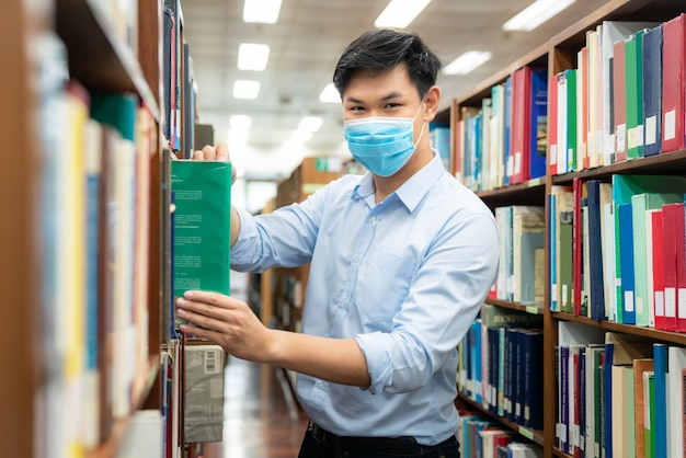 Aziatische universiteitsstudentjongen die medisch gezichtsbeschermend masker draagt voor bescherming tegen virusziekte Premium Foto