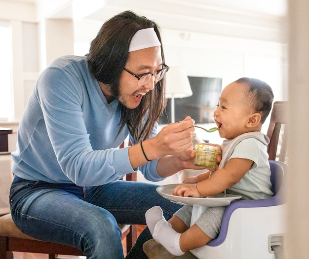 Aziatische vader die zijn zoontje voedt met puree Gratis Foto