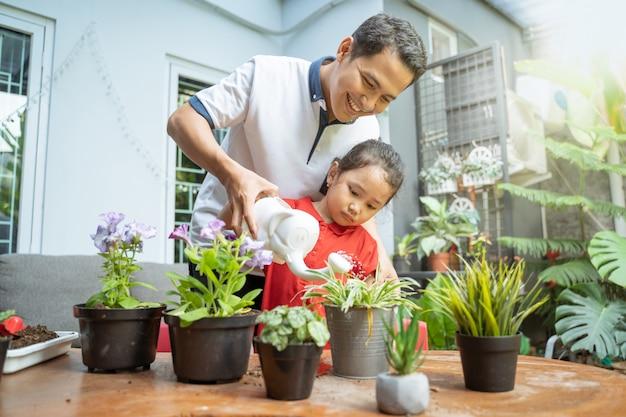Aziatische vader en dochter die gieter gebruiken om potplanten water te geven Premium Foto