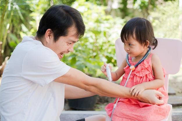 Aziatische vader en dochter speelrol van arts en patiënt, Premium Foto