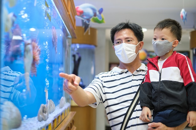 Aziatische vader en kind dragen van beschermende medische masker tijdens covid-19 uitbraak Premium Foto