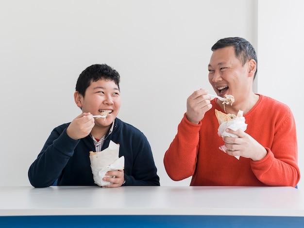 Aziatische vader en zoon samen eten Gratis Foto