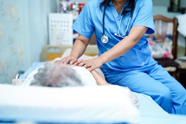 Aziatische verpleegkundige fysiotherapeut arts zorg, hulp en ondersteuning senior of oudere oude dame vrouw patiënt liggen in bed op ziekenhuis ward Premium Foto