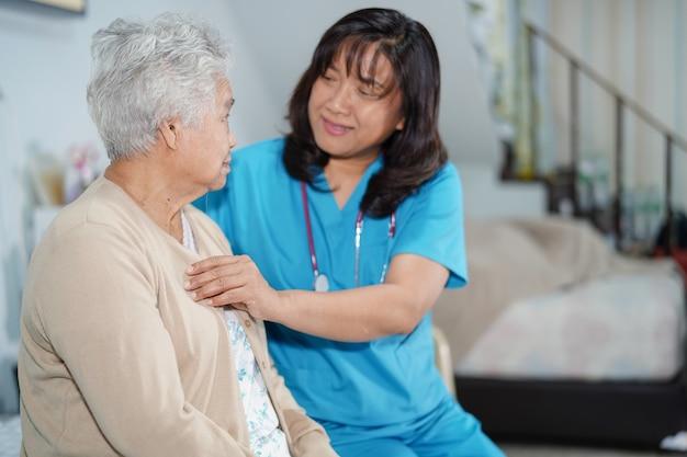 Aziatische verpleegsterszorg, hulp en steun hogere vrouwenpatiënt in het ziekenhuis. Premium Foto