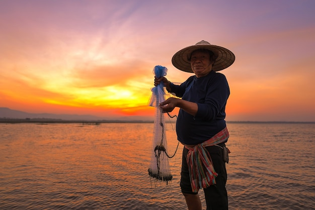 Aziatische visser in aardrivier bij de vroege ochtend vóór zonsopgang Premium Foto