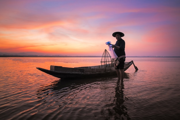 Aziatische visser met zijn houten boot in aardrivier bij de vroege ochtend vóór zonsopgang Premium Foto