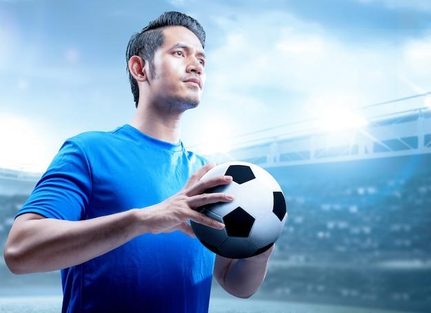 Aziatische voetbalstermens die de bal op het voetbalgebied houdt Premium Foto