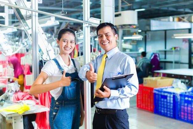 Aziatische voorman in textielfabriek die opleiding geeft Premium Foto