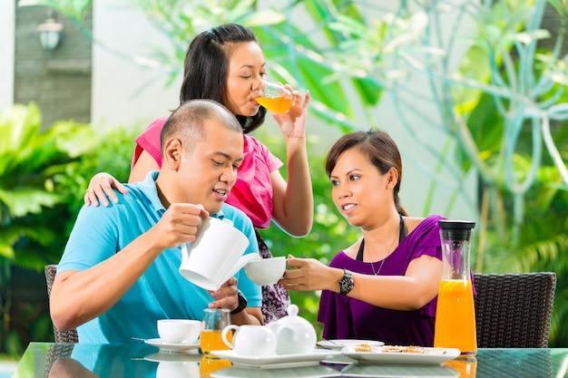 Aziatische vrienden die koffie op huisportiek hebben Premium Foto