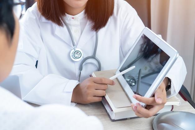 Aziatische vrouw arts handen gebruik stylus wijst tablet-monitor voor leg uit aan de patiënt. Premium Foto