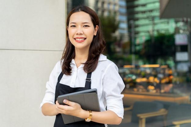 Aziatische vrouw barista bedrijf tablet voor het controleren van de bestelling van de klant op wazig koffie café winkel Premium Foto