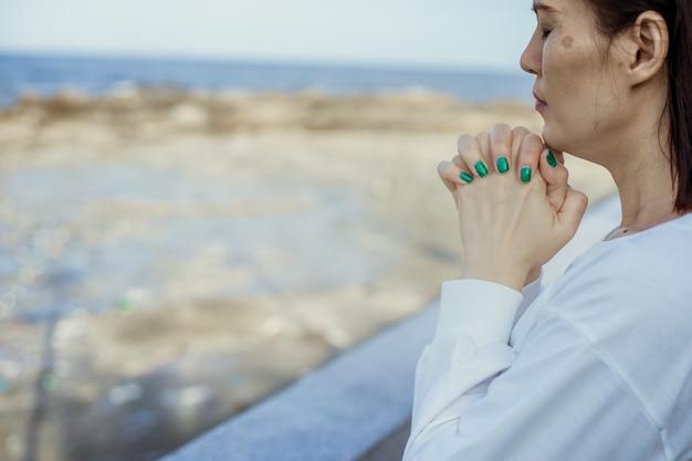 Aziatische vrouw bidden tot god buiten. Premium Foto