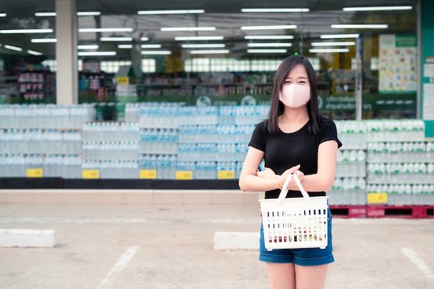Aziatische vrouw die aan een supermarkt met een beschermend gezichtsmasker winkelt en een mand houdt Premium Foto
