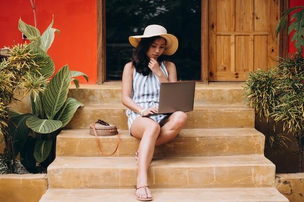 Aziatische vrouw die aan laptop op een vakantie werkt en op de treden zit Gratis Foto