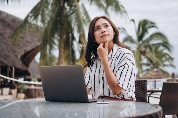 Aziatische vrouw die aan laptop op een vakantie werkt Gratis Foto