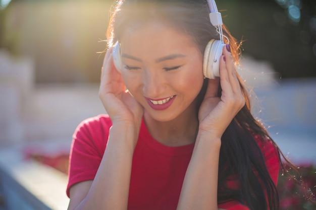 Aziatische vrouw die aan muziek luistert Premium Foto