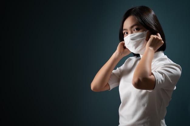 Aziatische vrouw die beschermend masker draagt voor bescherming tegen virussen en ziekten die op blauw worden geïsoleerd Premium Foto