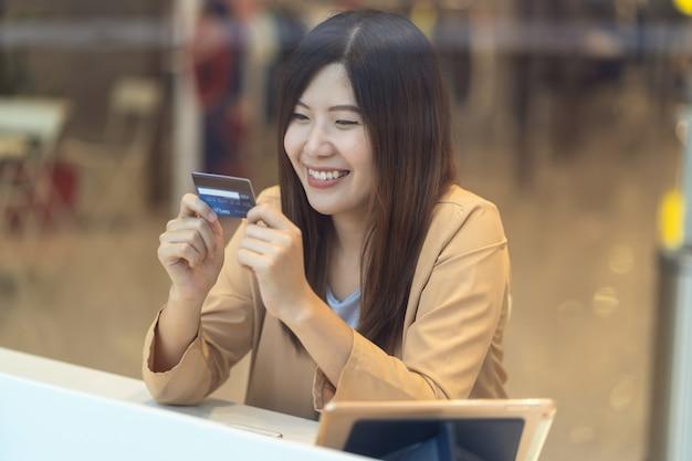 Aziatische vrouw die creditcard met mobiele telefoon voor online het winkelen in warenhuis met behulp van Premium Foto