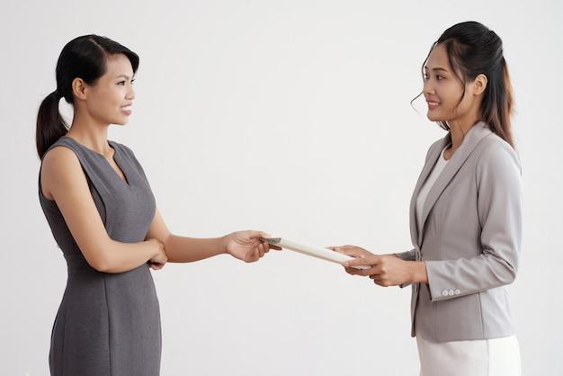 Aziatische vrouw die documentomslag geeft aan haar vrouwelijke werkgever in pak op het werk Gratis Foto