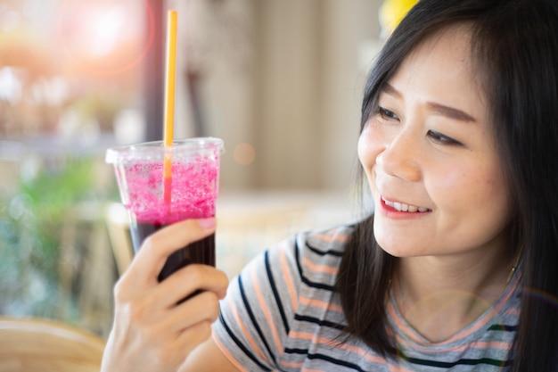 Aziatische vrouw die een bietensap met gelukkig houden, concept in gezond eten. Premium Foto