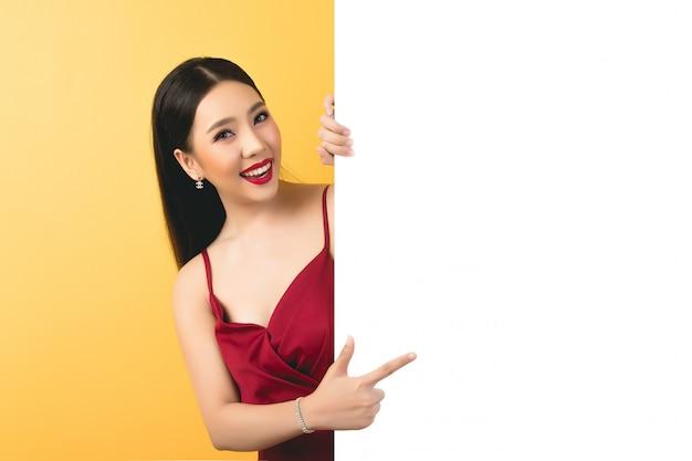 Aziatische vrouw die en omhoog aan toespraakbel houden kijken met lege ruimte voor tekst Gratis Foto