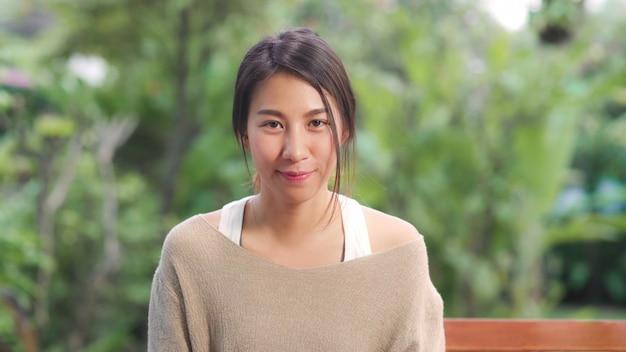 Aziatische vrouw die het gelukkige glimlachen voelen en kijken terwijl thuis ontspannen op lijst in tuin in de ochtend. lifestyle vrouwen ontspannen thuis concept. Gratis Foto