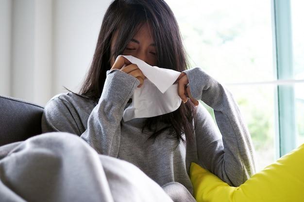 Aziatische vrouw die in weefsel niest. ziekte, liggend op de bank Premium Foto