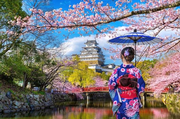 Aziatische vrouw die japanse traditionele kimono draagt die kersenbloesems en kasteel in himeji, japan bekijkt. Gratis Foto