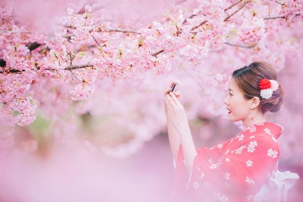 Aziatische vrouw die kimono draagt die smartphone met kersenbloesems, sakura in japan gebruikt. Premium Foto