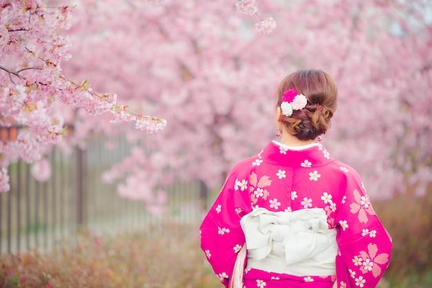Aziatische vrouw die kimono met kersenbloesems draagt, sakura in japan. Premium Foto