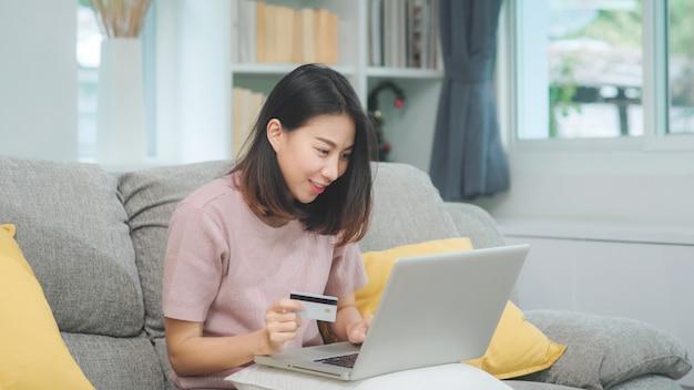 Aziatische vrouw die laptop en creditcard het winkelen elektronische handel, wijfje gebruikt ontspant thuis het voelen van gelukkige online het winkelen zitting op bank in woonkamer. lifestyle vrouwen ontspannen thuis concept. Gratis Foto