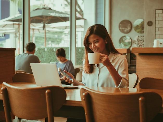 Aziatische vrouw die met laptop in de koffie van de koffiewinkel werkt Premium Foto