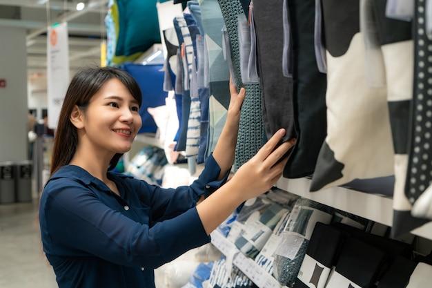 Aziatische vrouw die nieuwe hoofdkussens in de wandelgalerij kiest te kopen. Premium Foto