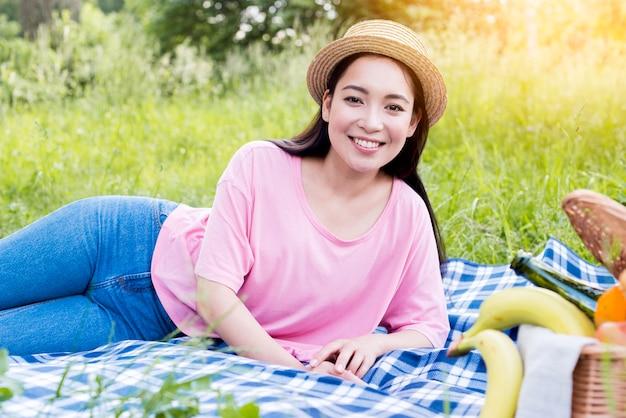 Aziatische vrouw die op picknickdoek ligt Gratis Foto