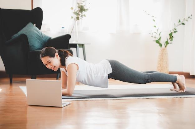 Aziatische vrouw die plankoefening thuis in een woonkamer doet Premium Foto