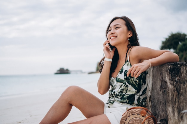 Aziatische vrouw die telefoon gebruikt bij het strand op een vakantie Gratis Foto