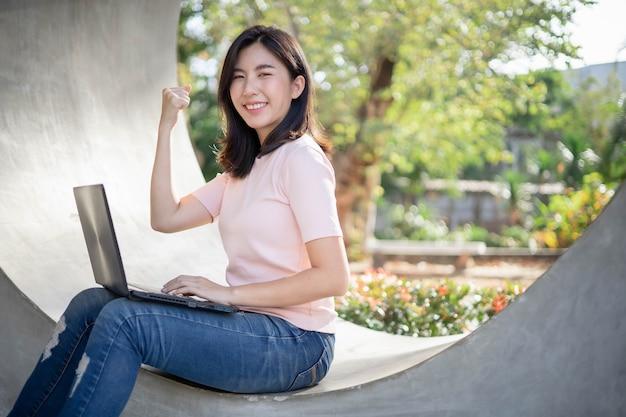 Aziatische vrouw die werk door notitieboekje controleert Premium Foto